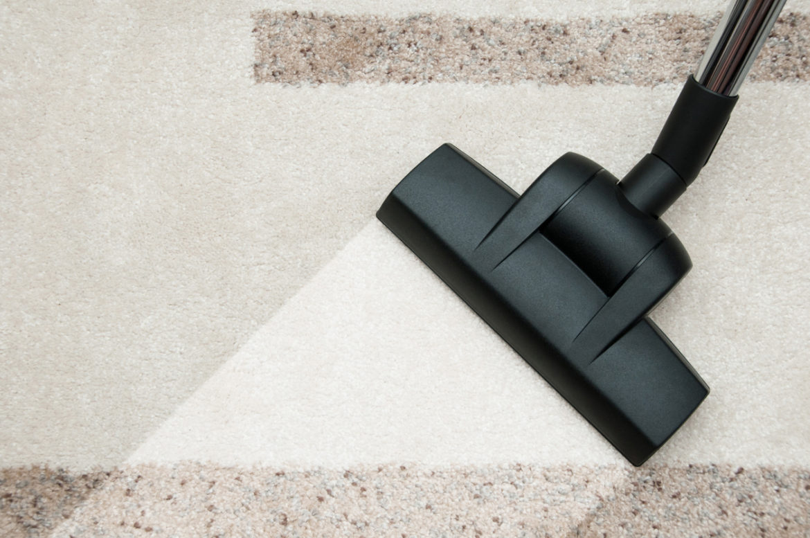 Close Up Of Vacuum Cleaner Nozzle Cleaning Carpet At Home
